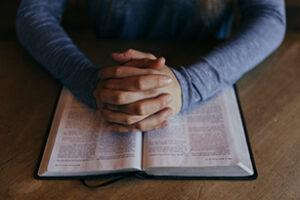 This image has an empty alt attribute; its file name is Bible-w-hands-praying-307x205-72-ppi-300x200.jpg