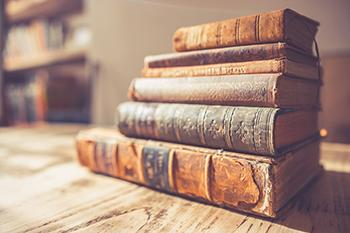 This image has an empty alt attribute; its file name is old-books-on-table-350x233-72-ppi.jpg